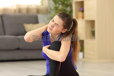 sportlerin leidet zu hause unter nackenschmerzen