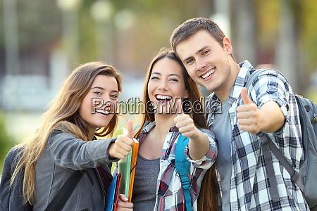 drei glueckliche schueler mit daumen hoch