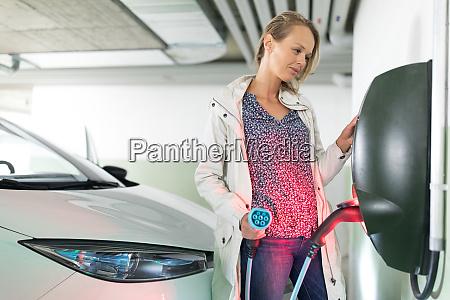junge frau laedt ein elektrofahrzeug in