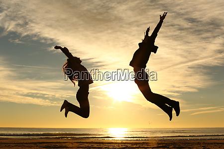 ehepaar oder freunde springen bei sonnenuntergang