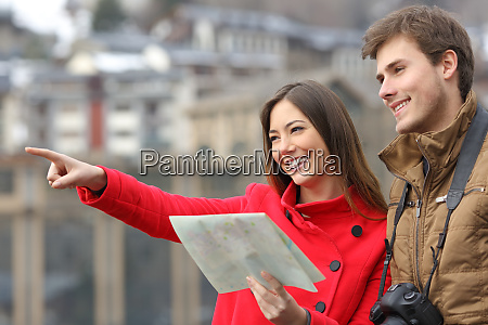 couple of tourists holding map and