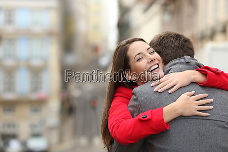 cheerful couple meeting and hugging in