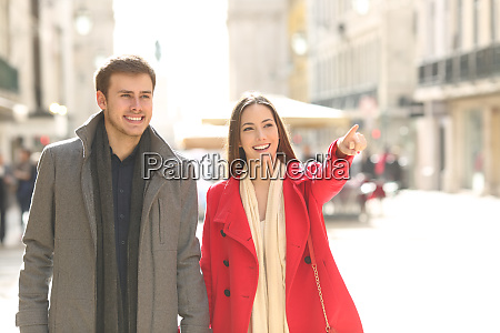 couple walking in the street pointing