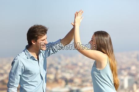 glueckliche freunde geben hohe fuenf im