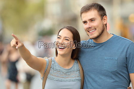 happy couple finding location and pointing