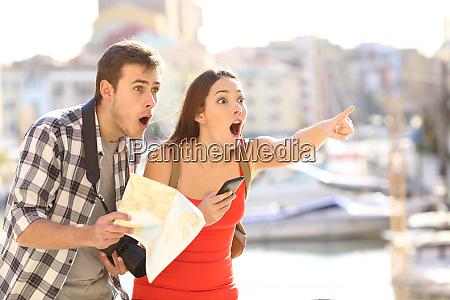 amazed couple of tourists finding destination
