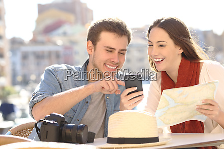 couple of tourists comparing online guide