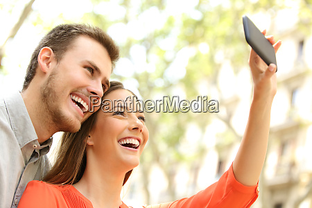 happy couple taking selfies in the