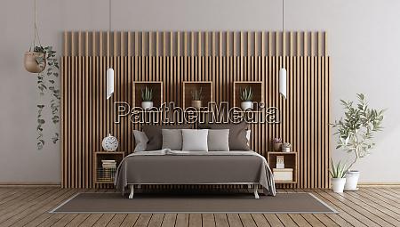 hauptschlafzimmer mit bett gegen holzvertaefelung