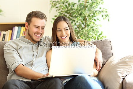 happy couple using a laptop on