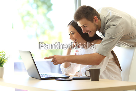couple searching online in a laptop