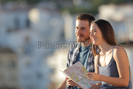 happy couple of tourists holding map