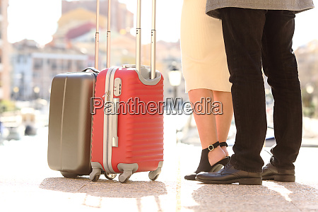 travelers legs and suitcases in a