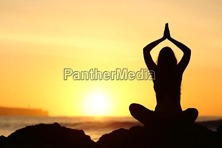 woman silhouette doing yoga exercises
