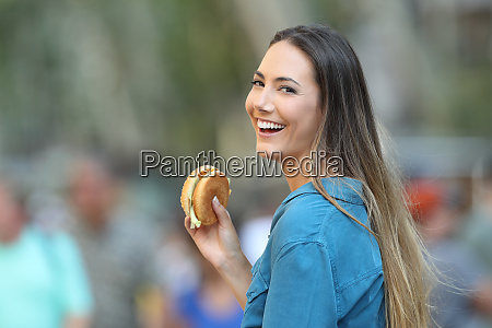 happy woman holding a burger looking