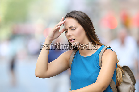 woman suffering headache outdoor in the