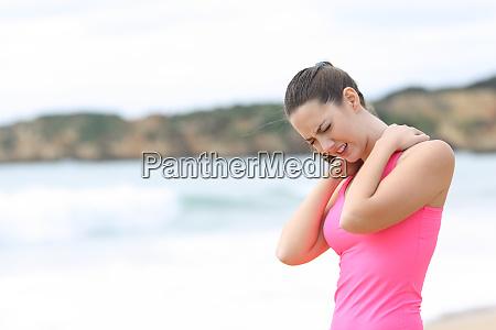 sportlerin leidet nackenschmerzen am strand