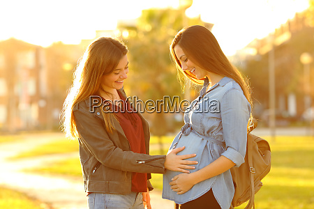 happy pregnant woman showing belly to