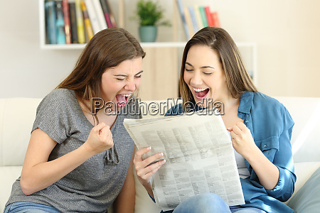 excited friends reading newspaper news