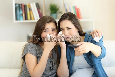 sad friends watching romantic movie on