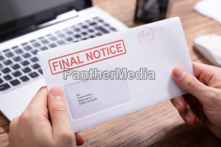 person holding final notice envelope