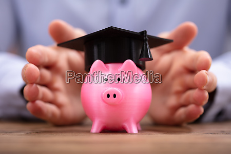 man protecting piggy bank with graduation