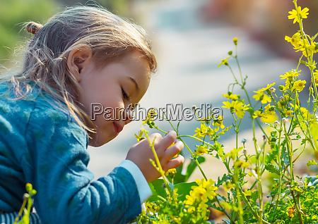 kleiner junge geniesst blumenaroma