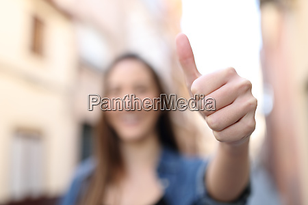 unfocussed woman gesturing thumb up in
