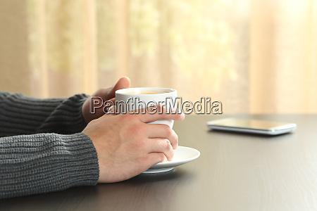 mann haende halten eine kaffeetasse auf