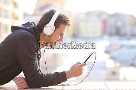 teenager junge musikhoeren mit telefon und