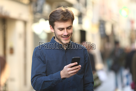 smiley man checking smart phone content