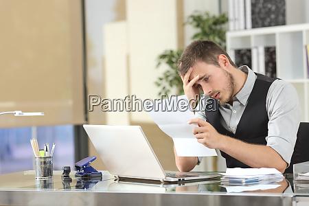 sad businessman reading a letter at