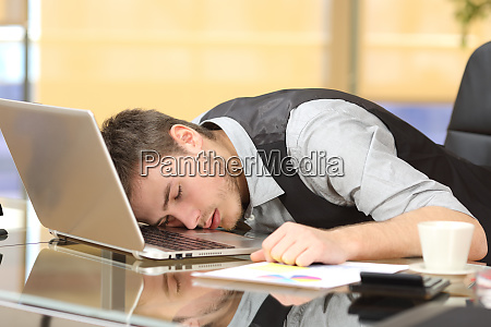 tired businessman sleeping over a laptop