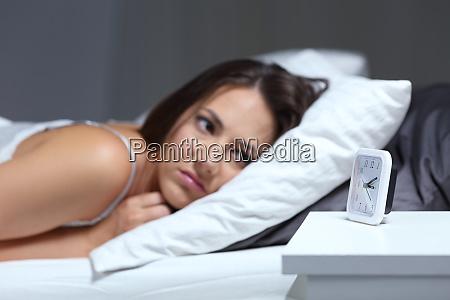 insomniac frau blickend auf wecker in