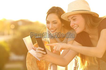 touristen ueberpruefen informationen online bei sonnenuntergang