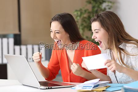 excited businesswomen reading good news