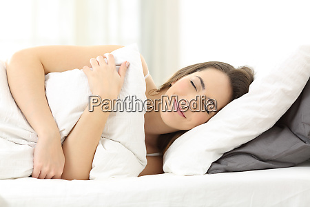 happy woman sleeping embracing a pillow