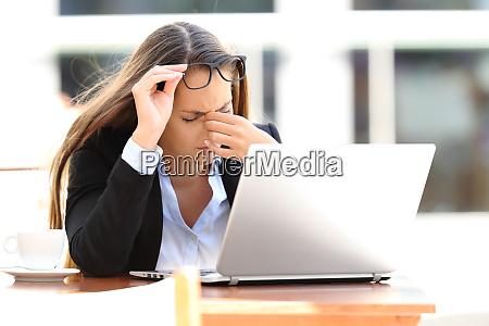 tired worker suffering eyestrain in a