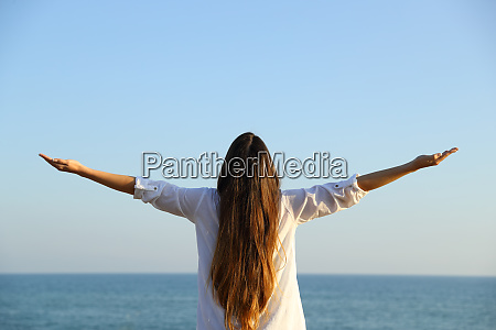 woman outstretching arms to the sea