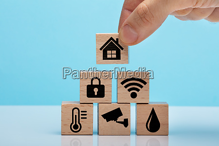 hand holding wooden block with home