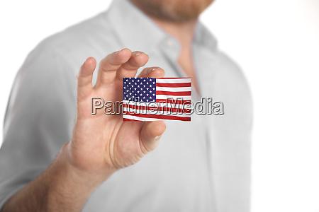 geschaeftsmann haelt visitenkarte mit usa flagge