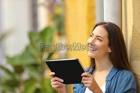 happy woman holding tablet thinking looking