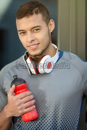 young latin man water bottle runner