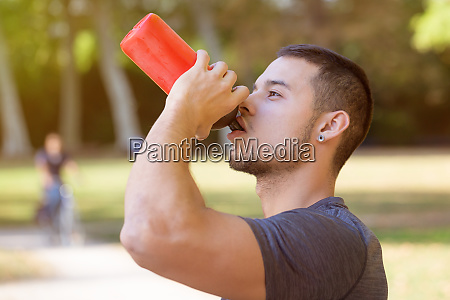 runner young latin man drinking water