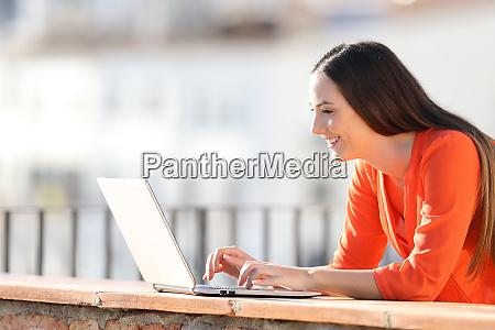 glueckliche frau schreibt auf laptop auf