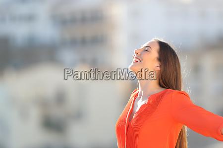 joyful woman in orange breathing deep