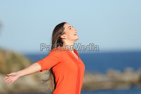 happy woman in orange breathing fresh
