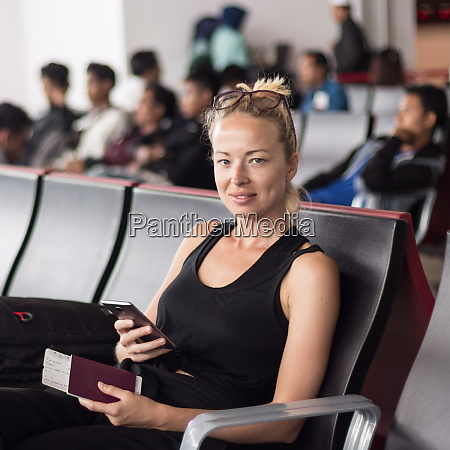 casual tanned blond female traveler holding