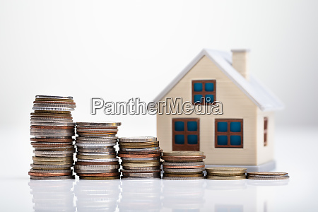 house model behind stacked coins