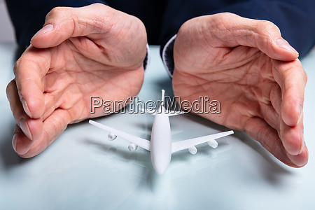 mans hand protecting the airplane
